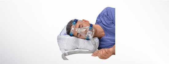 Man wearing CPAP Mask laying on specialized CPAP Bed Pillow